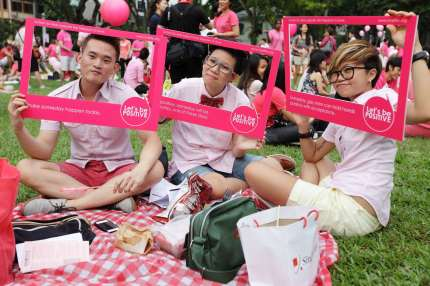 SINGAPORE - JUNE 30: Participants dress in various shades of pink, hold up placards during the 'Night Pink Dot' event arrange to increase awareness and understanding of the lesbian, gay, bisexual and transgender community in Singapore at Hong Lim Park on June 30, 2012 in Singapore. The event is the fourth annual gathering held in support of the freedom to love. (Photo by Suhaimi Abdullah/Getty Images)