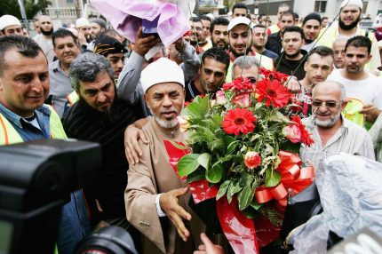 SYDNEY, AUSTRALIA - NOVEMBER 03: Controversial muslim cleric Sheik Taj el-Din al Hilaly offers flowers to the media after Friday prayers at Lakemba mosque November 3, 2006 in Sydney, Australia. Hilaly spoke at the prayers in his first public appearance since being hospitalized on October 30, 2006. The mufti has faced criticism in Australia following a sermon last month in which he suggested that immodestly dressed women invited sexual assault. (Photo by Ian Waldie/Getty Images)