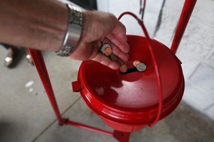 A donation is made into a Salvation Army red kettle