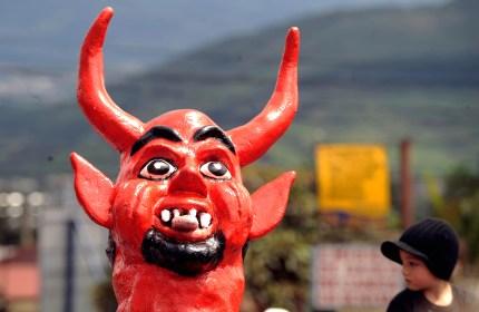 A photo of a man in a devil mask