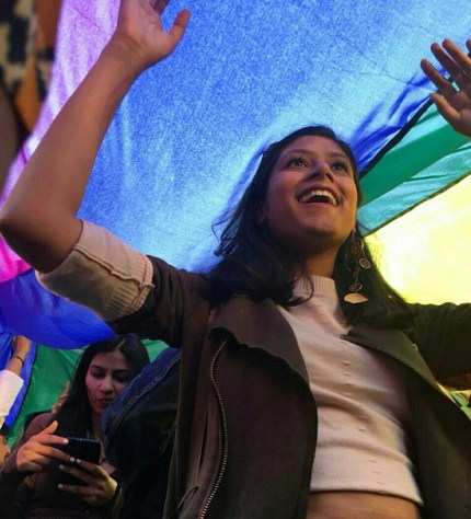 Attendee smiles with delight as they walk under a rainbow flag in the first Indian Pride parade since the decriminalisation of gay sex
