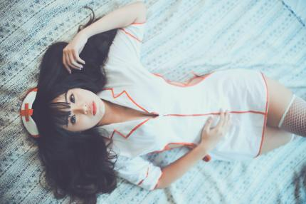 A woman lies on a bed in a nurse costume