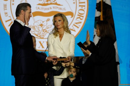 Gavin Newsom (L) is sworn in as governor of California by California Chief Justice Tani Gorre Cantil-Sakauye (R) as Newsom's wife, Jennifer Siebel Newsom (C), watches on January 7, 2019 in Sacramento, California