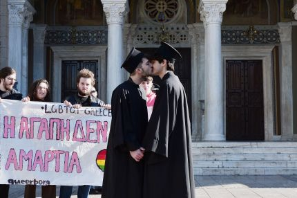 Gay rights activists dressed up as Orthodox priests kiss next to the Metropolitan church in Athens on December 22, 2015.