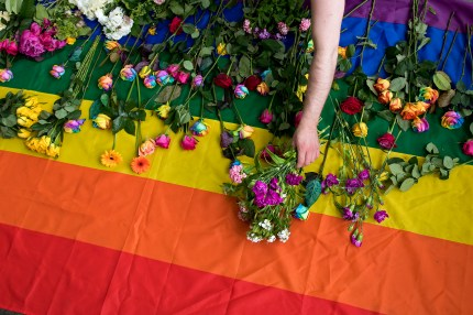 Demonstrators lay roses on a rainbow flag as they protest over an alleged Chechnya anti-gay purge outside the Russian Embassy in London on June 2, 2017.