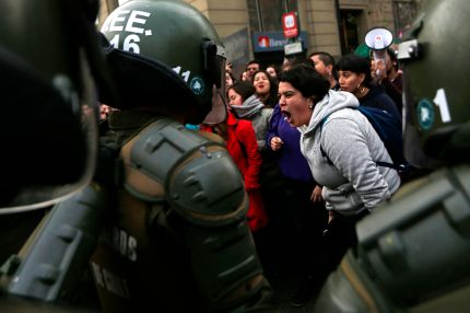 """Pro-choice and gay, lesbian, bisexual and trans activists argue with riot police as the bus chartered by """"Hazte Oir"""" (Make yourself heard) conservative association passes by La Moneda presidential palece in Santiago in 2017, the same year the girl was allegedly raped"""
