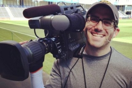Scott Winer poses with a camera in a sports ground