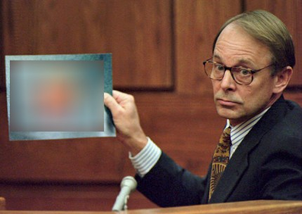 Dr. James T. Sehn holds a photo of the severed penis of John Wayne Bobbitt, which his wife had previously sliced off, during the second day of the malicious wounding trial of Lorena Bobbitt in the Prince William Circuit Court in Manassas, VA, 11 January 1994. Dr. Sehn and a team of surgeons reattached the penis in a nine-hour operation.