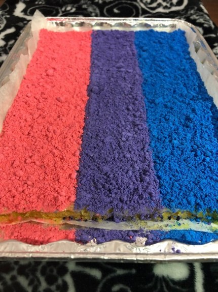 Bisexual lemon bars: A collection of lemon bars decorated in the colours of the bisexual flag.