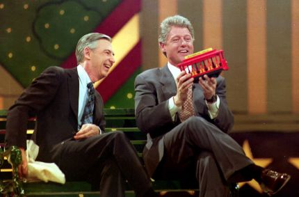 """U.S. President-elect Bill Clinton (R) holds a trolley car given to him by Fred Rogers (L) during the Presidential Inaugural Celebration for Children 19 January 1993 at the Kennedy Center. Fred Rogers was the host of the children's show """"Mister Rogers' Neighborhood""""."""