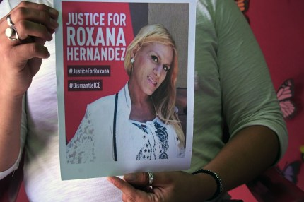 A member of the Pink Unity Collective holds a photo of Roxana Hernandez.