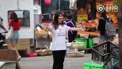 Woman protesting for LGBT+ rights to tackle Weibo's censoring of LGBT+ content.