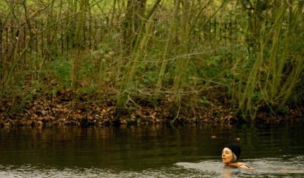 A woman swimming in Hampstead Heath wearing a cap