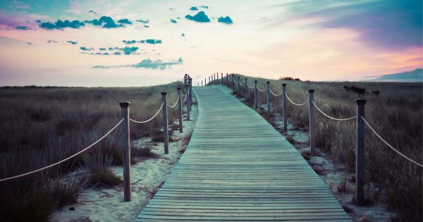 A walkway made of wood extends over a sandy, grassy hill in to the sunset.
