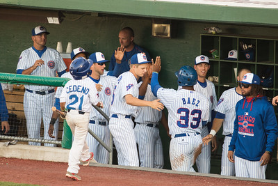 Jeffrey Baez is congratualated by his teammates after scoring a run for the South Bend Silverhawks on July 22, 2015