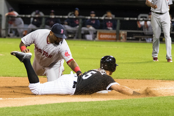 Carlos Sanchez slides into third while Pablo Sandoval applies the tag during the Chicago White Sox game against the Boston Red Sox on August 25, 2015