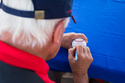 Baseball Hall of Fame pitcher Phil Niekro signs a ball for a fan prior to the Indianapolis Indians game against the Charlotte Knights on August 1, 2015