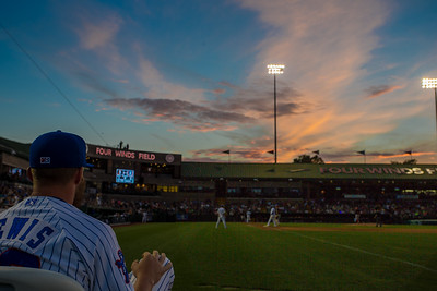 Daniel Lewis of the South Bend Cubs watches the game as the sun sets in the background.