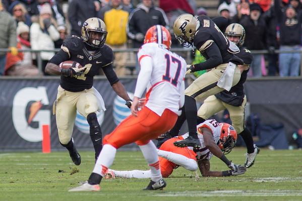Akeem Hunt (1) looks for running room as Robert Gregory (7) of Purdue jumps over Jevaris Little (15) of Illinois