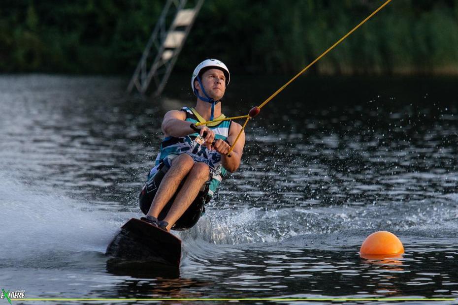Człowiek na desce, trzymający rączkę liny, sunie po tafli wody