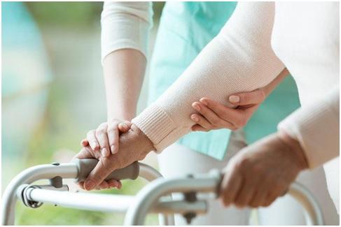 Na zdjęciu seniorka poruszająca się o balkoniku. Obok jej opiekunka.