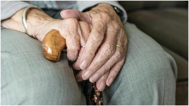 Na zdjęciu dłonie starszej osoby wsparte na lasce