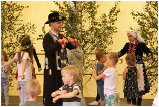 Tancerze w strojach ludowych z grupą dzieci