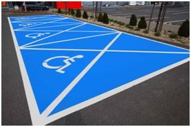 Na zdjęciu niebieska koperta - miejsce parkingowe przeznaczone dla osób z niepełnosprawnością
