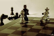 man-riding-a-knight-figure-on-a-chess-board.