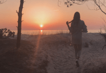 Orange sunset in Palanga beach. Amazing view. girl walking on a beach.