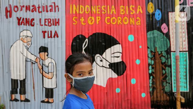 Seorang anak kenakan masker dengan latar belakang mural Indonesia Bisa Stop Corona di Lapangan Bulutangkis, Kampung Kali Pasir, Jakarta(Liputan6.com/Feri Pradolo)