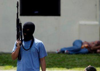 "Seorang teroris tiruan memegang senapan di dekat ""warga sipil yang ditahan"" dalam latihan anti-teror di markas pasukan khusus polisi di Depok, Jawa Barat, 9 Maret 2010. (Foto: REUTERS/Beawiharta)"