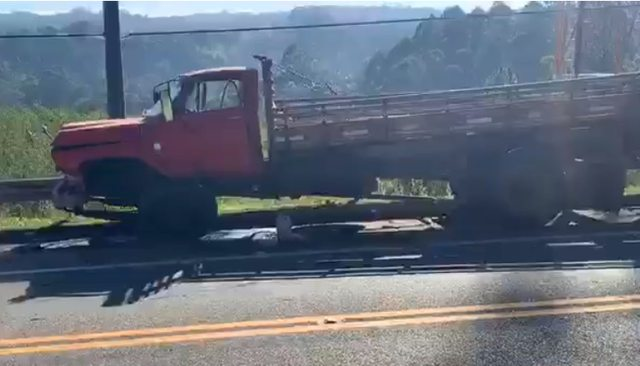 A imagem mostra o caminhão. Ele é vermelho e perdeu a roda superior direita no acidente.