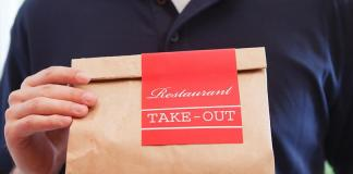 A man holding a brown paper bag that is marked Restaurant Take-Out