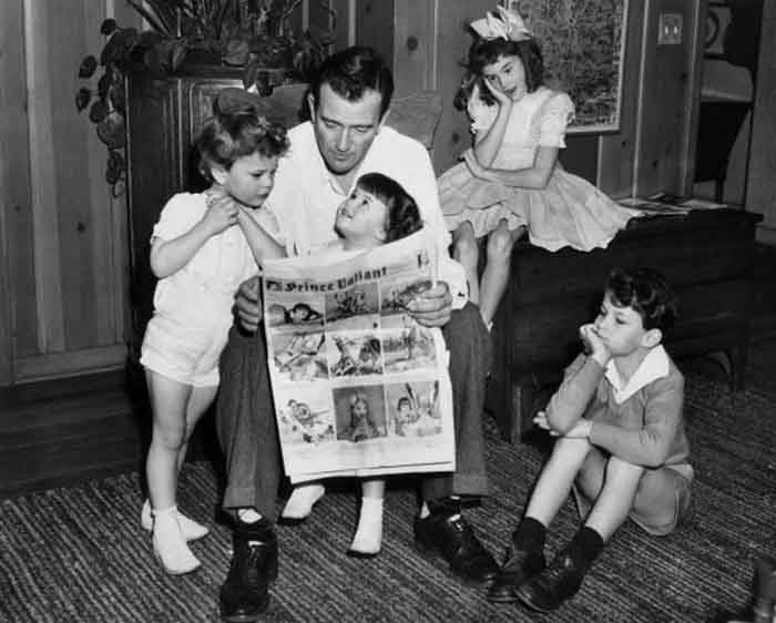 1942:  American actor John Wayne sitting on a chair and reading a Prince Valiant comic with his four children, Hollywood, California.  From left: Patrick, Melinda, Toni, and Michael.  Patrick and Melinda are leaning on their father, while the other two children listen from a desk and the floor.  (Photo by Hulton Archive/Getty Images)