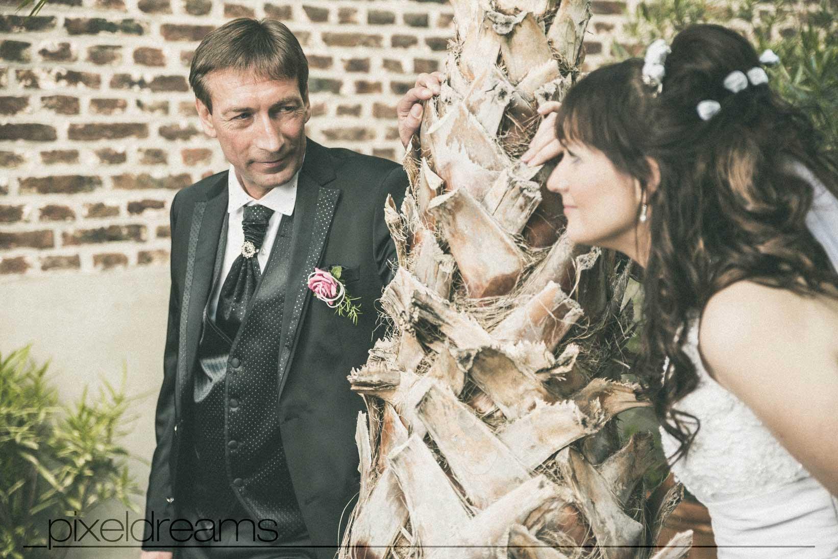braut und bräutigam stehen an einer palme und tauschen zärtlichen Blicke aus während der sie fotografiert werden