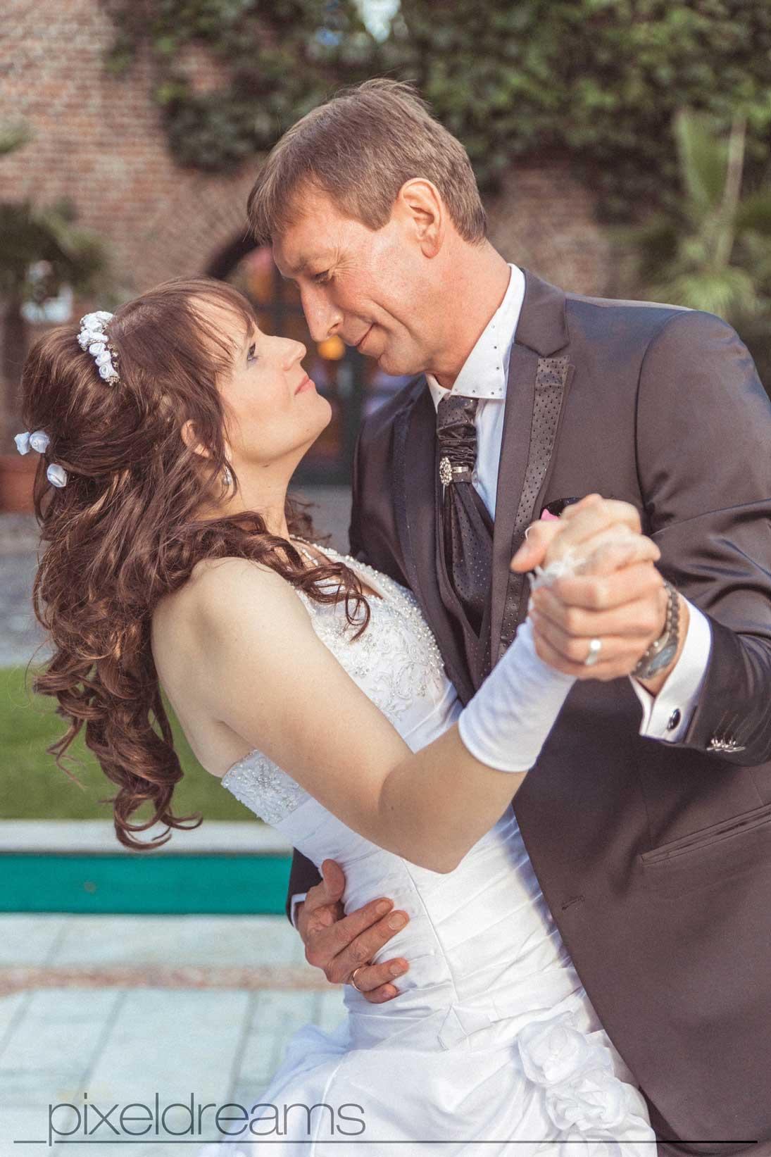 Das Brautpaar tanzt im Gutshof während der Hochzeitsfotograf sie dabei fotografiert.