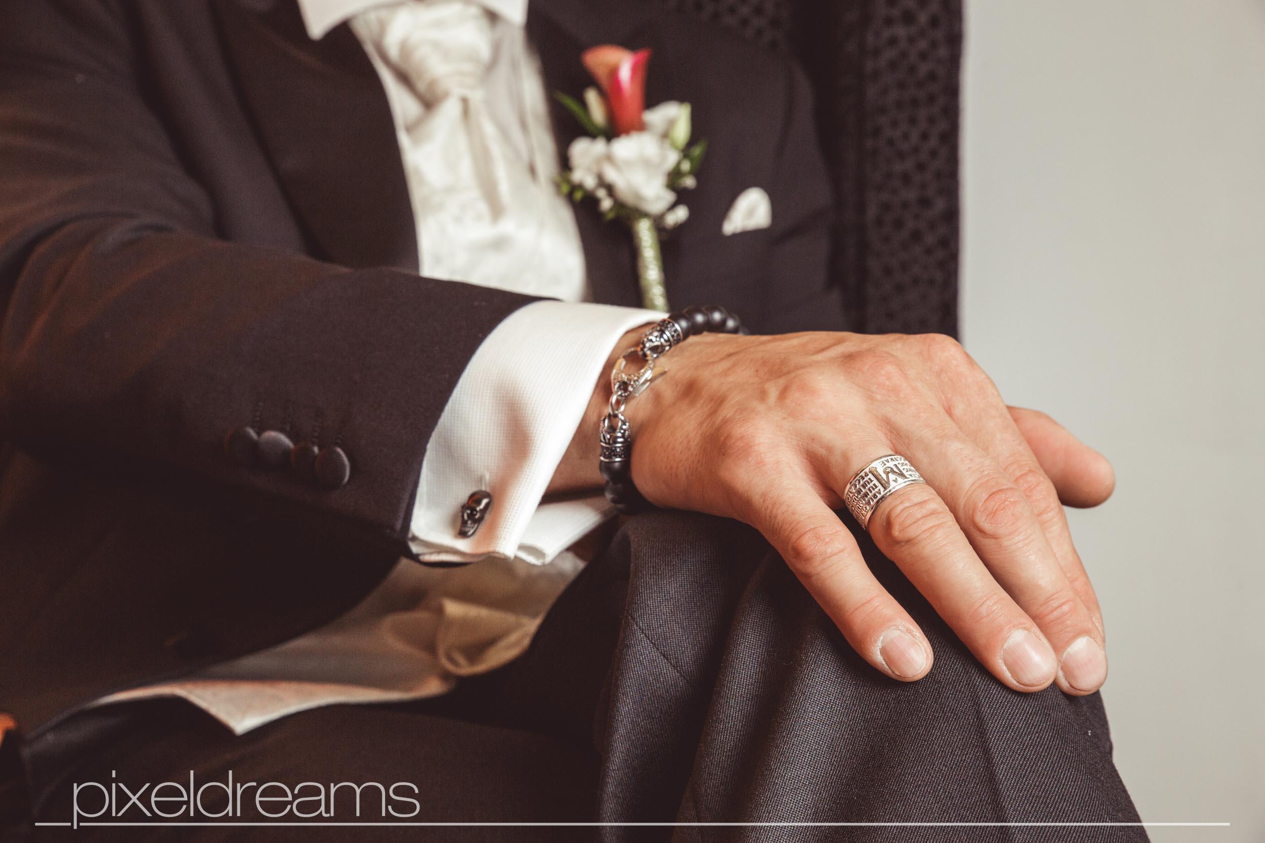 Bräutigam sitzt und wartet auf die Braut. Sein außergewöhnlicher Trauring steht im Focus- Hochzeitsfotos vom Hochzeitsfotografen Pixeldreams
