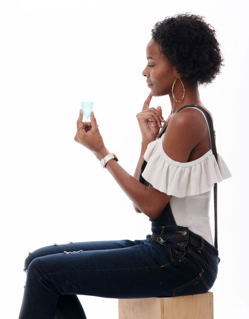girl holding pixie menstrual cup pondering
