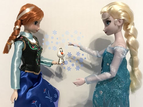 Anna and Elsa dolls with mini Olaf figure.