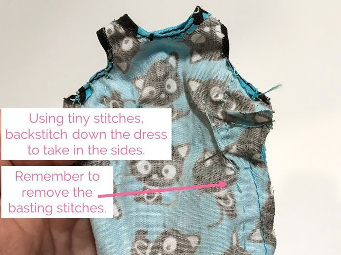 Using a backstitch and small stitches, sew up the sides of the dress.