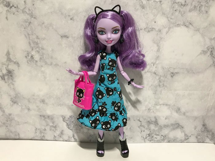 Kitty Cheshire wearing Hello Kitty dress, headband, and tote.
