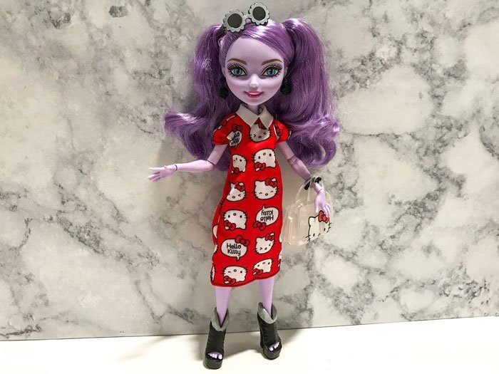 Kitty Cheshire wearing the red Hello Kitty dress.