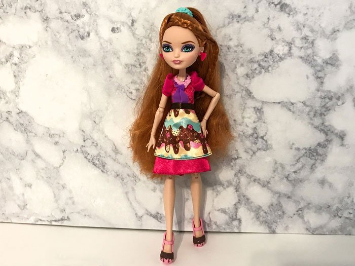 Sugar Coated Holly O'Hair comes wearing a dress, apron, and pink shoes.
