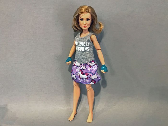 Yes. Hasbro's Captain Marvel dolls can wear Barbie clothes.