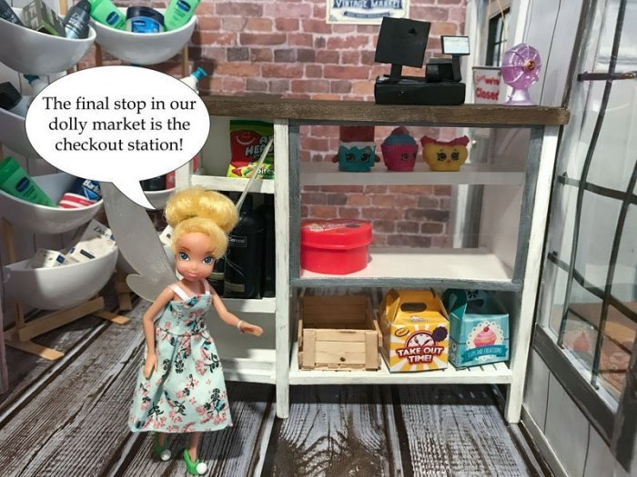 Tinkerbell showing off our DIY doll checkout counter.