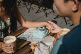 couple having coffee in outdoor cafe during trip together