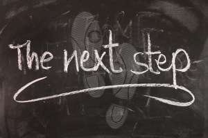"Chalkboard with ""the next step"" written on it and footprints on board"