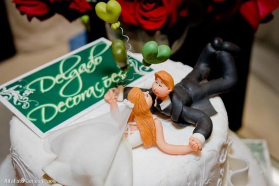Noivinhos de topo de bolo deitados de bruços, dando um beijo, da Delgado Decorações