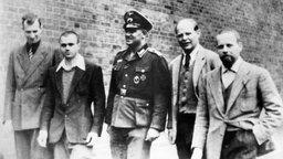 Schwarzweiß-Aufnahme: Bonhoeffer (Zweiter von rechts) und drei Mitinsassen laufen über den Gefängnishof in Berlin-Tegel. In der Mitte in Uniform: Oberfeldwebel Napp, der die Fotoaufnahme veranlasst hat.